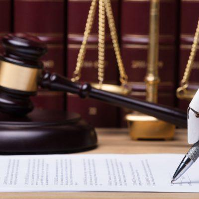 Eine Roboterhand unterschreibt ein juristisches Dokument