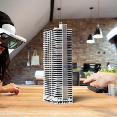 Mitarbeiter eines Architekturbüros studieren den digitalen Zwilling eines geplanten Hochhauses