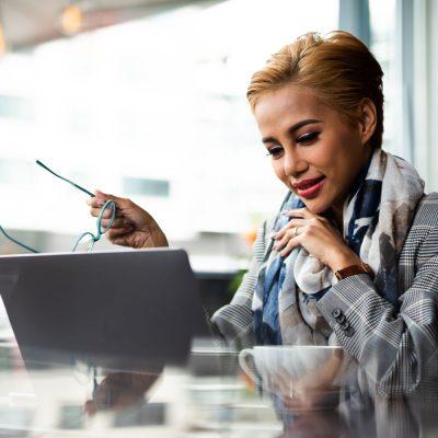 Junge Geschäftsfrau nutzt Skype for Business in einem Café