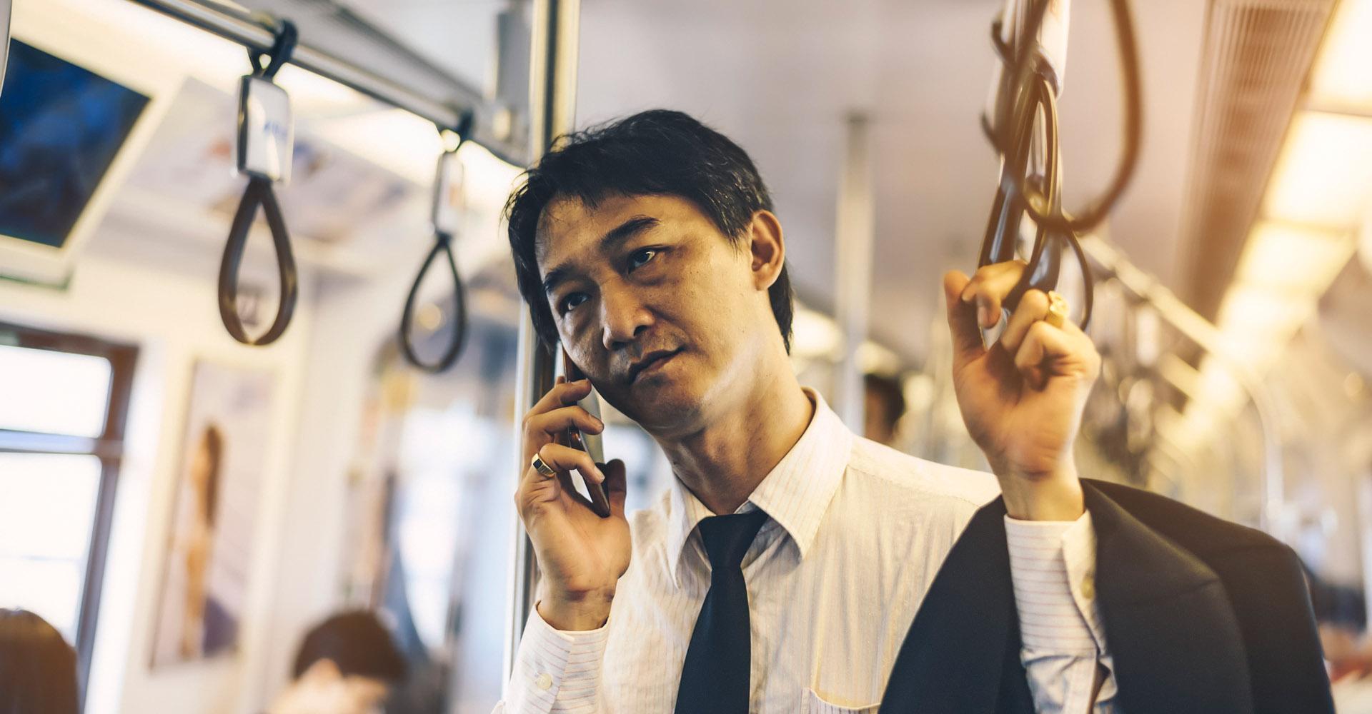 Pendler telefoniert genervt in einer U-Bahn