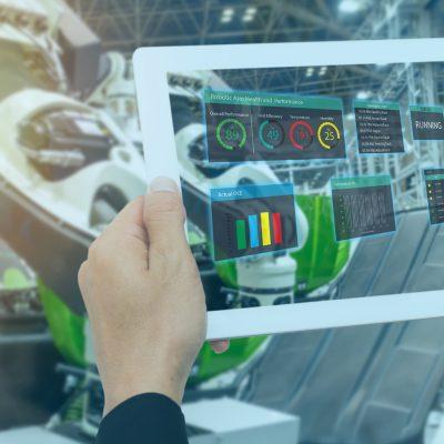 Ein Tablet zeigt Statistiken der Smart Factory dahinter