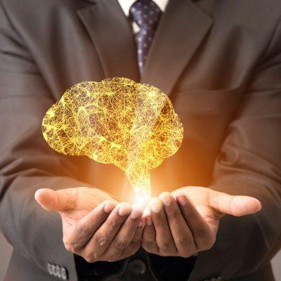 Symbolbild mit elektronischem Gehirn in einer Hand