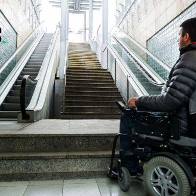 Ein Rollstuhlfahrer sieht sich mit einer Treppe konfrontiert.