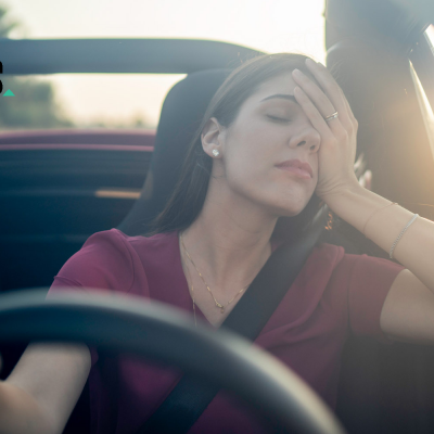 Geschäftsfrau sitzt müde im Auto