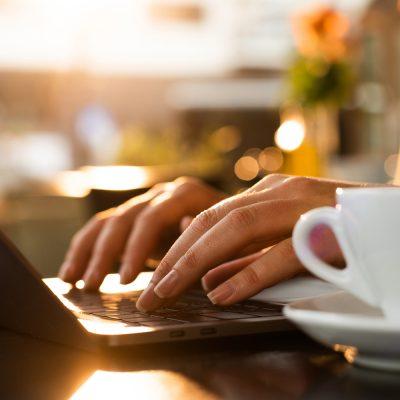 Kreative arbeitet am Laptop und trinkt Kaffee