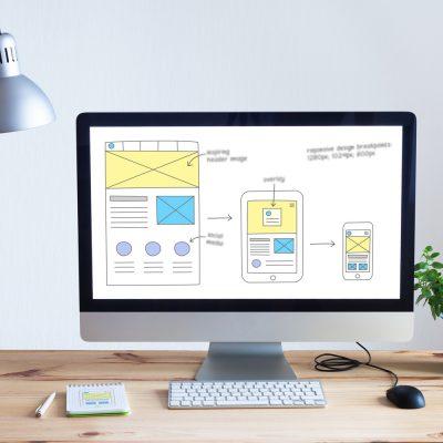 Schreibtisch mit einem Computer und einer Grafik zum Thema Webdesign