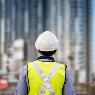 Bauarbeiter blickt auf ein Gebäude in der Ferne
