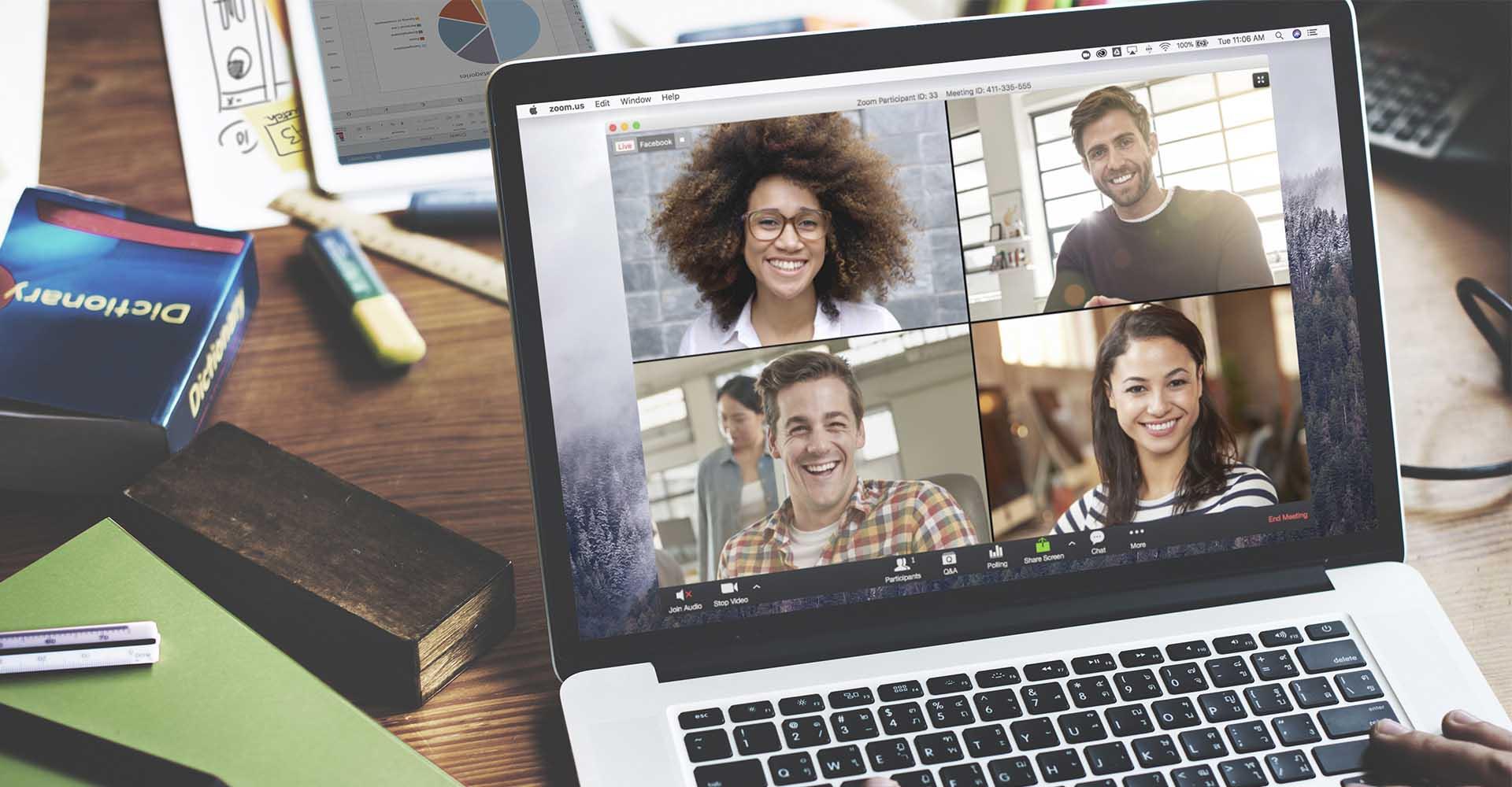 Ein Mann unterhält sich mit vier Personen via Videokonferenz auf seinem Notebook