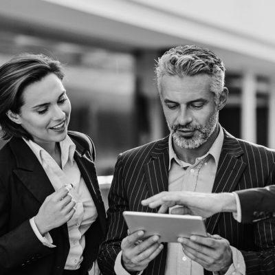 Drei Geschäftsleute betrachten den Bildschirm eines Tablets.