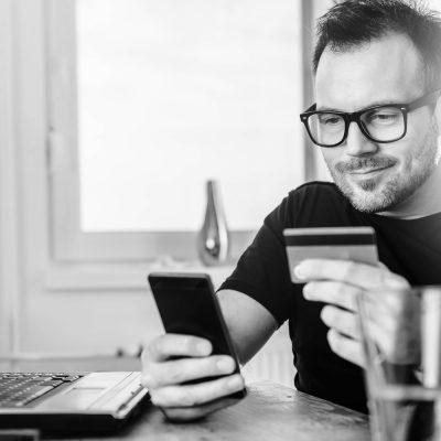 Ein junger Mann am Schreibtisch bezahlt einen Einkauf per Smartphone mit seiner Kreditkarte.