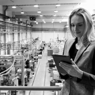 Junge Frau kontrolliert die Maschinen eines Unternehmens via Tablet