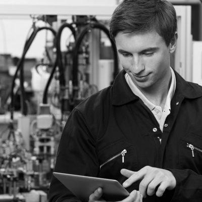 Junger Werksmitarbeiter prüft den Status einer Maschine an seinem Tablet.