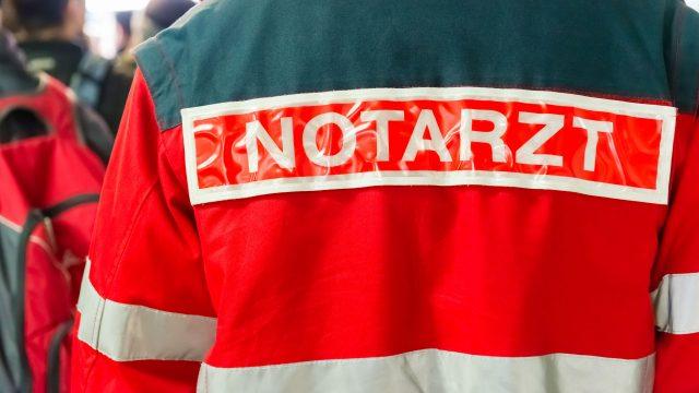 Ein Notarzt, dessen Jacke mit Aufschrift man von hinten sieht.