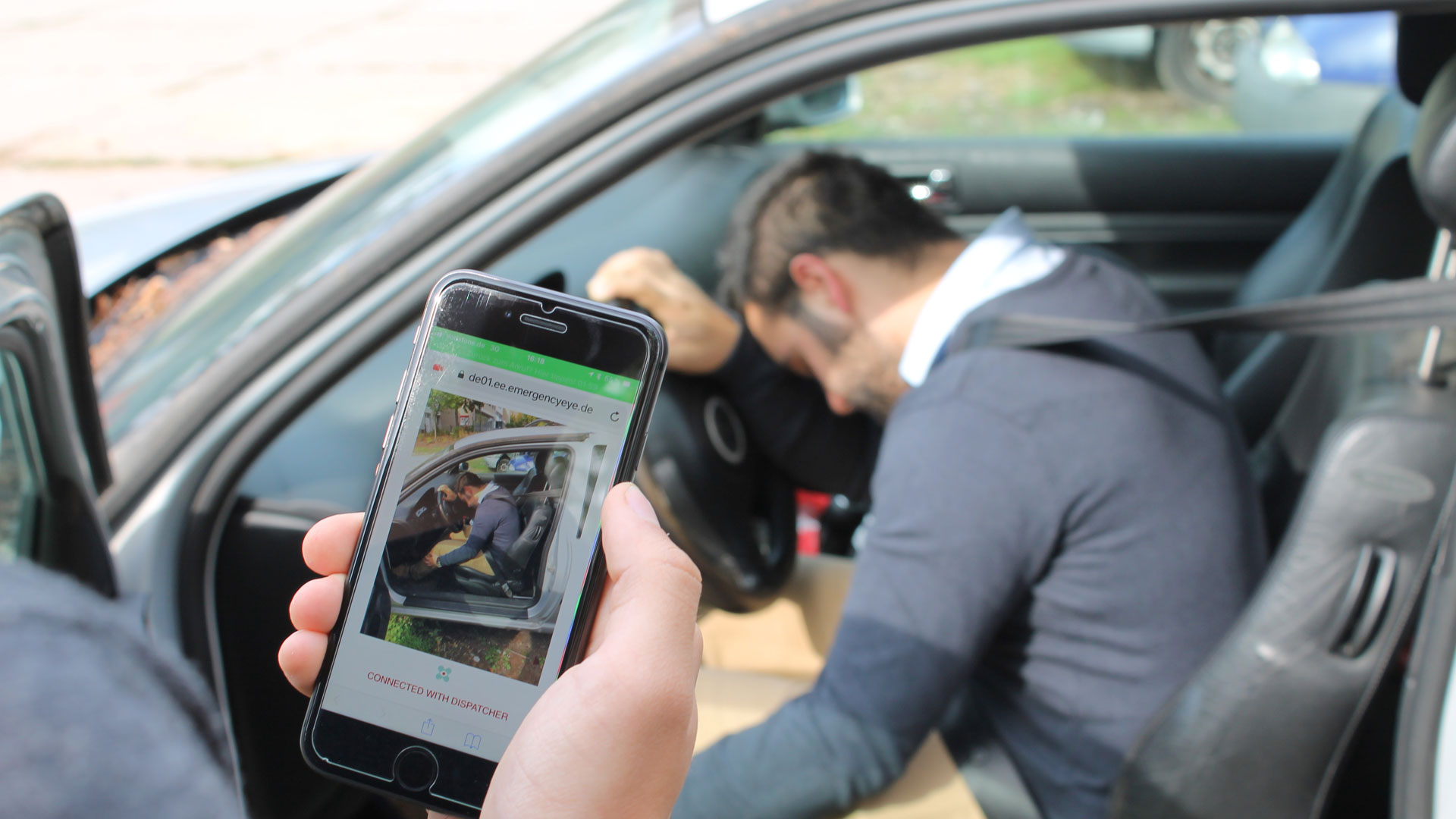 Ein Mann ruft mithilfe der Technologie EmergencyEye über sein Smartphone den Notruf, um einem bewusstlosen Autofahrer zu helfen.