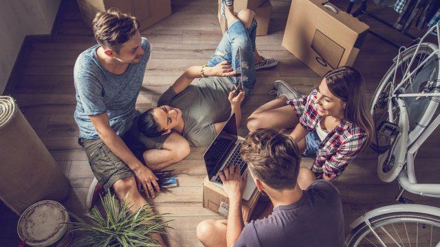 Vier junge Leute, die sich über WG-Portale gefunden haben, sitzen auf dem Boden zwischen Umzugskartons