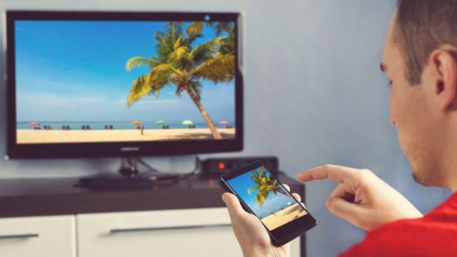 Mann sieht sich Urlaubsfotos vom Handy auf dem TV an