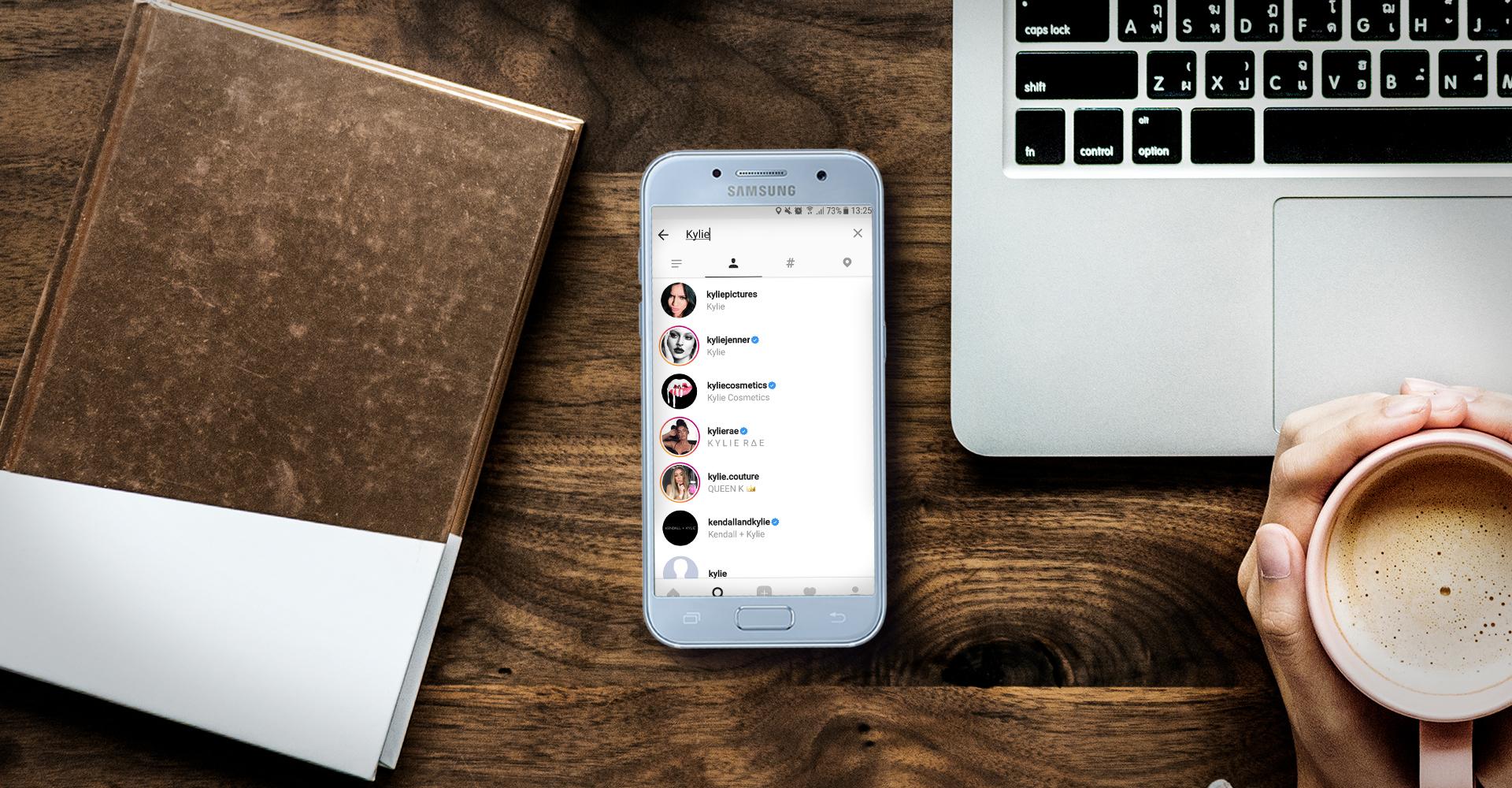 Samsung-Smartphone mit Instagram-Screenshot liegt neben dem Laptop auf dem Schreibtisch.
