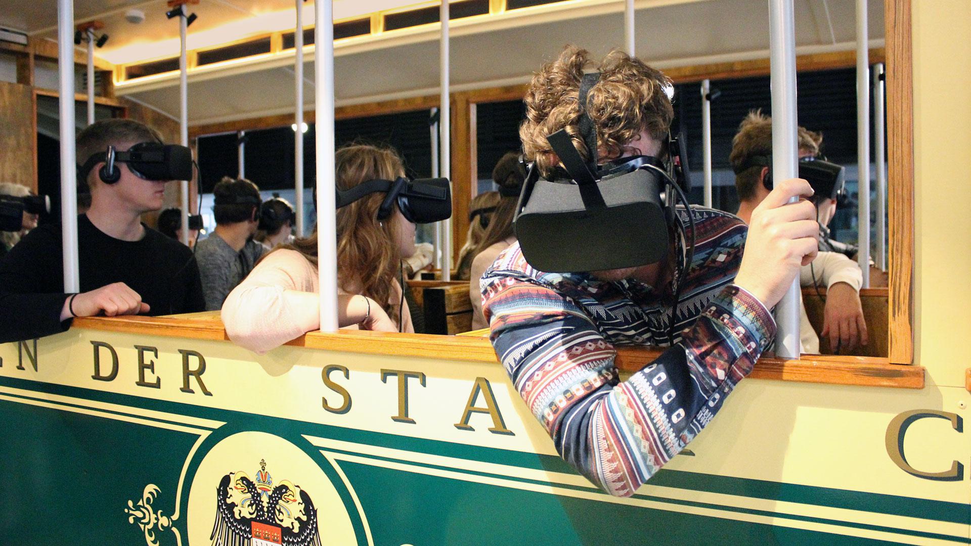 Menschen sitzen mit VR-Brillen in einer historischen Straßenbahn bei der VR-Zeitreise von Timeride in Köln.