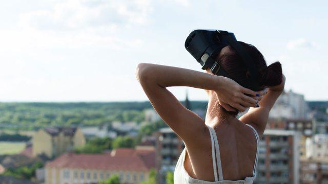 Eine Frau mit VR-Headset steht auf dem Dach und legt die Arme in den Kopf, im Hintergrund sieht man Häuser und Dächer einer Stadt.