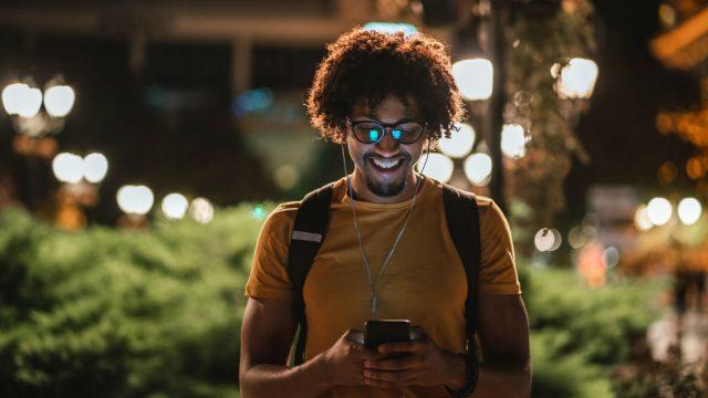 Junger Mann testet am Smartphone den Nachtmodus von WhatsApp.