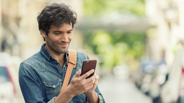 Mann liest Facebook-Nachrichten auf seinem Smartphone