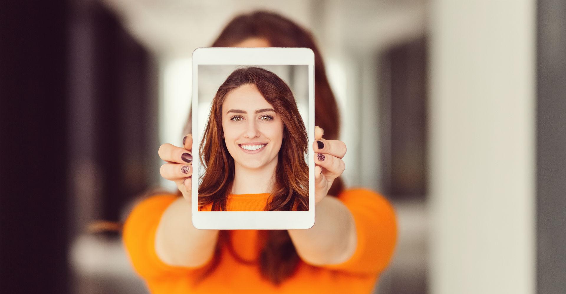 Frau hält eigenes Porträtfoto auf Tablet in die Kamera