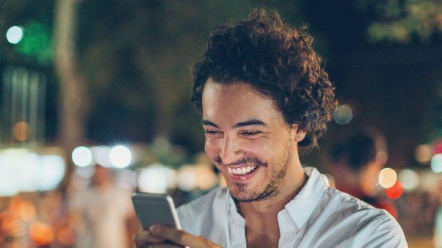 Junger Mann stellt an seinem Smartphone eine App wieder her.