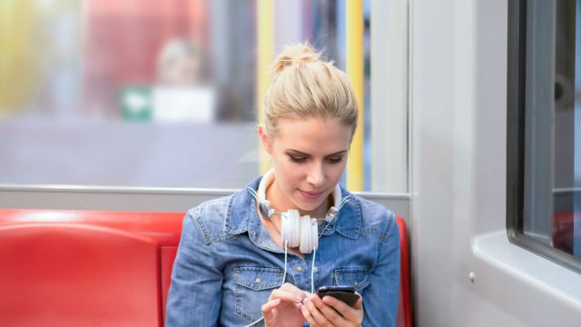Frau mit Smartphone in der Bahn
