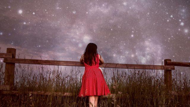 Mädchen lehnt an Zaun vor Sternenhimmel