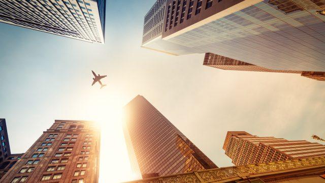 Flugzeug von unten zwischen Wolkenkratzern