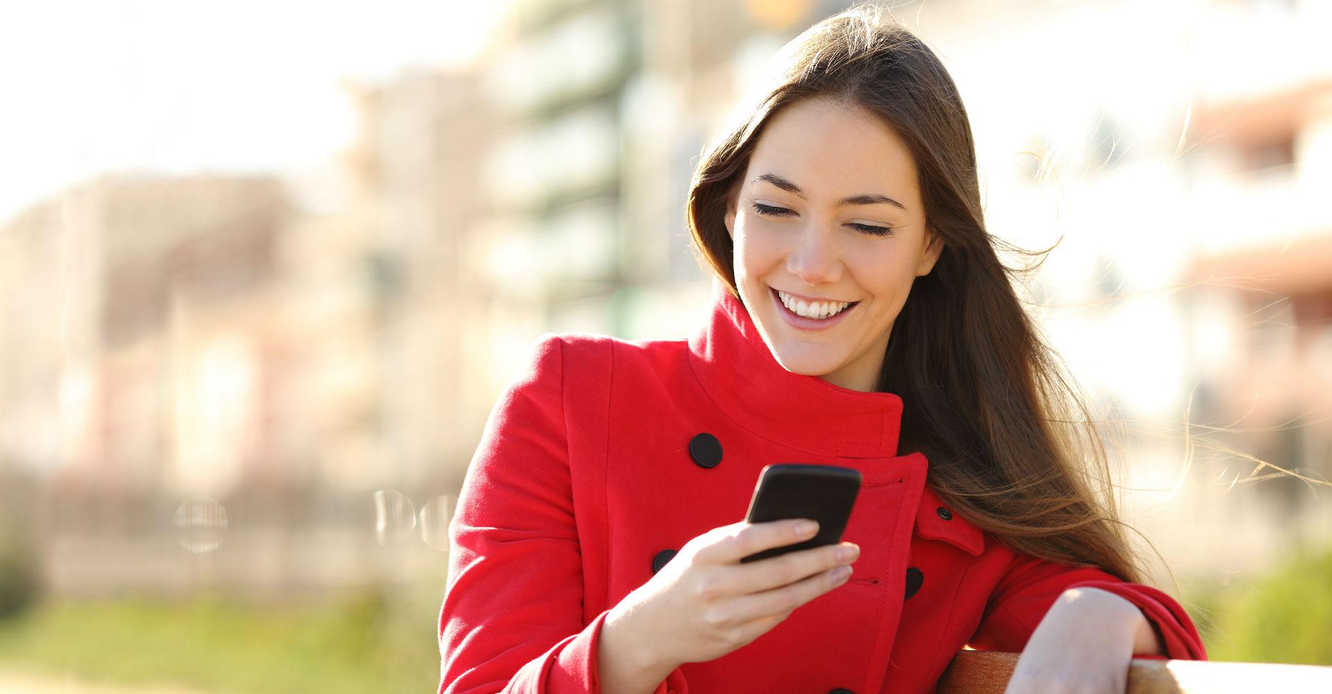 Frau im roten Mantel mit Smartphone in der Hand