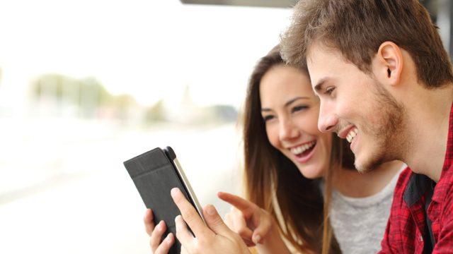 Junges Paar spielt draussen auf dem iPad