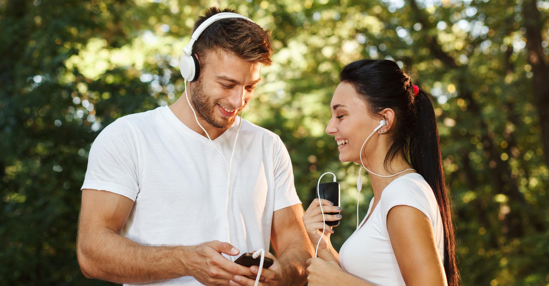 Mann und Frau beim Joggen mit verschiedenen Kopfhörersystemen