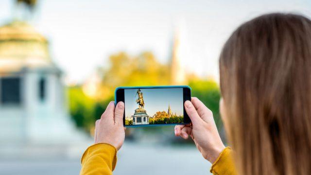 Junge Frau macht ein HDR-Foto mit dem Smartphone.