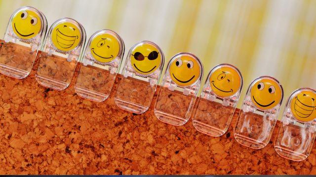 Verschiedene Emojis als Klammern an einem Korkbrett