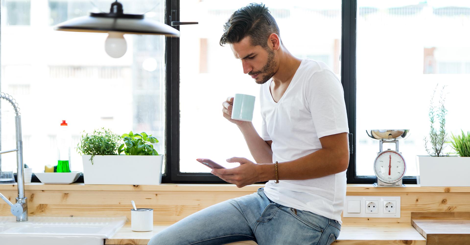 Mann schaut sich Smartphone an.