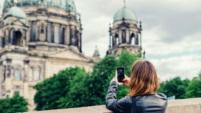 Frau schießt ein Foto vom Berliner Dom mit dem Smartphone