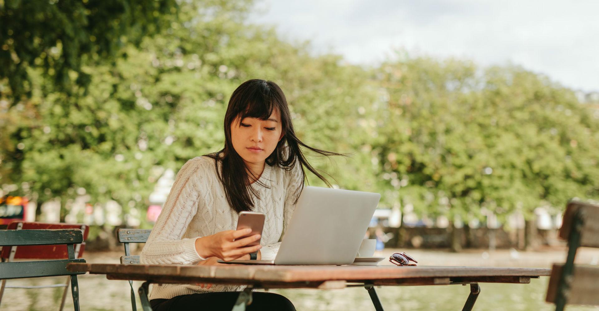 Frau sitzt draußen und schaut auf ihr Smartphone.
