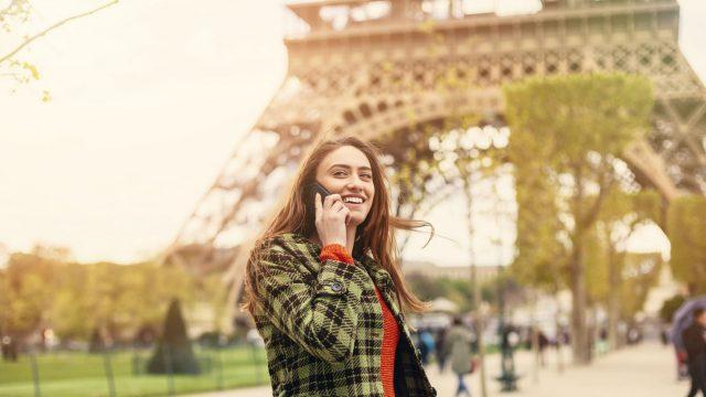 Frau telefoniert am Eiffelturm mit dem Smartphone.