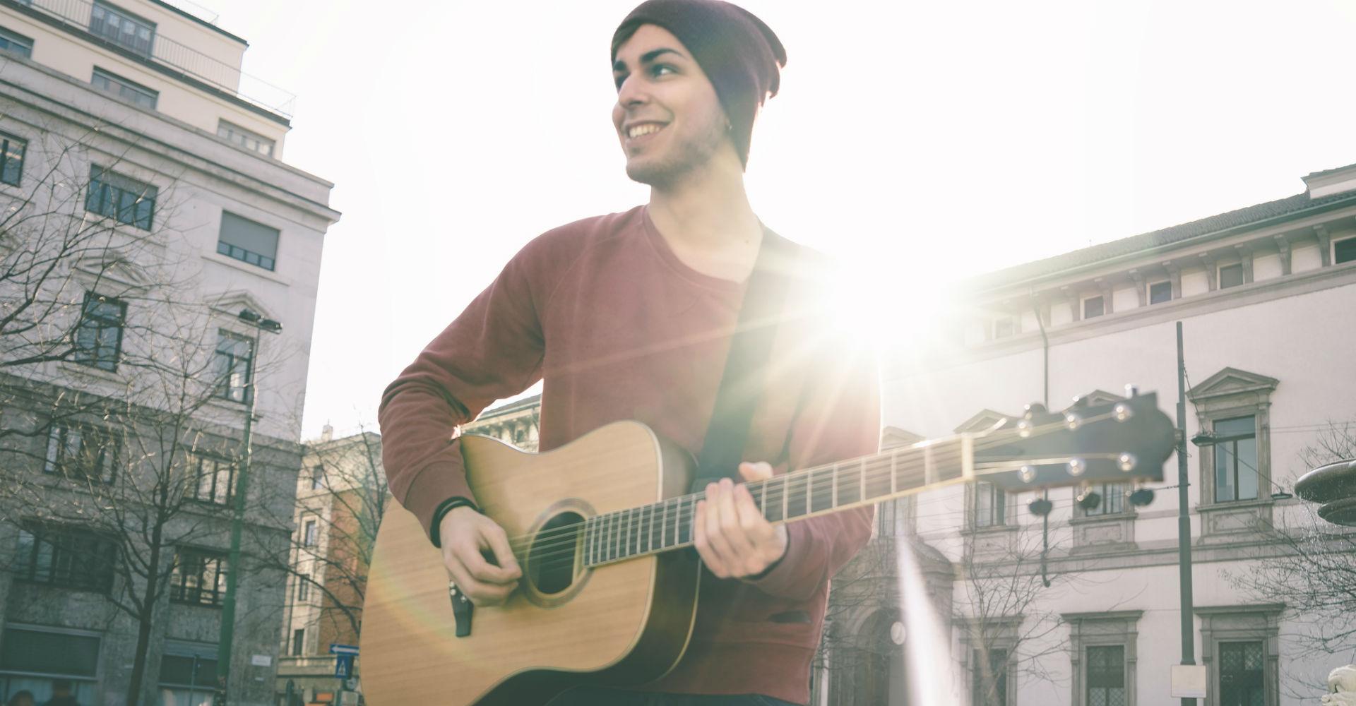 Junger Mann spielt Gitarre.