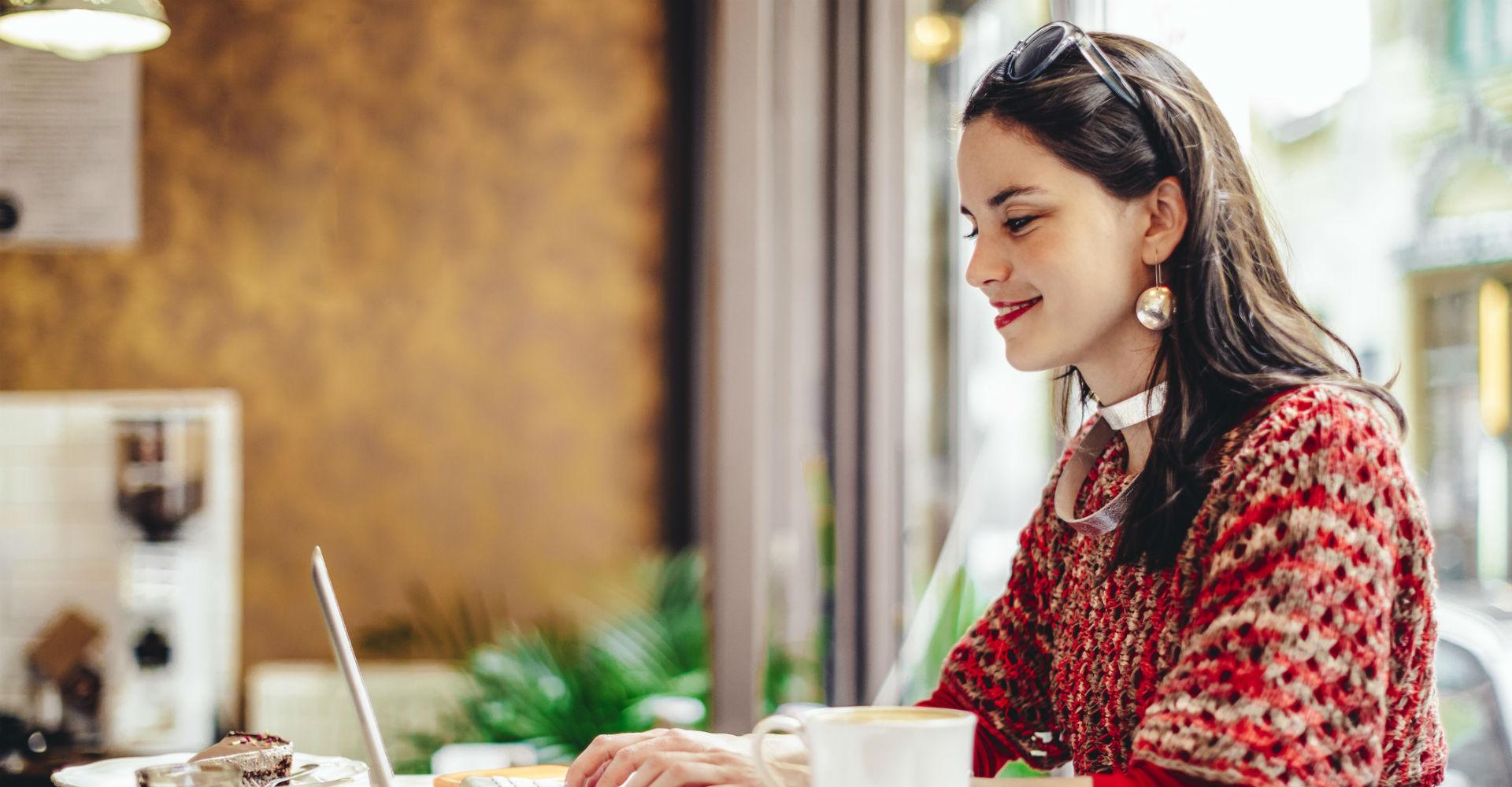 Junge Frau in roter Kleidung und Kaffee sitzt vor dem Laptop.