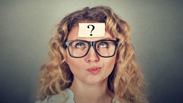 Verwirrter Frau klebt ein Fragezeichen auf der Stirn.