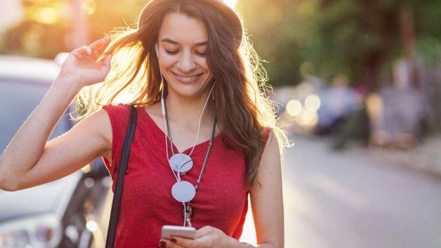 Mädchen in rotem Shirt mit Smartphone in der Hand.
