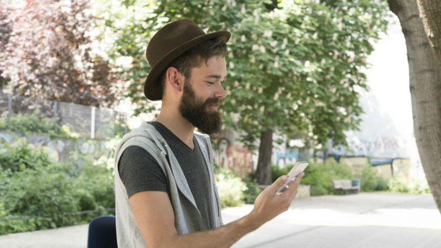 Junger Mann mit Bart hält Smartphone in der Hand.