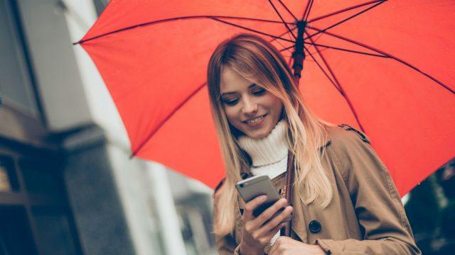Frau mit Regenschirm und Smartphone