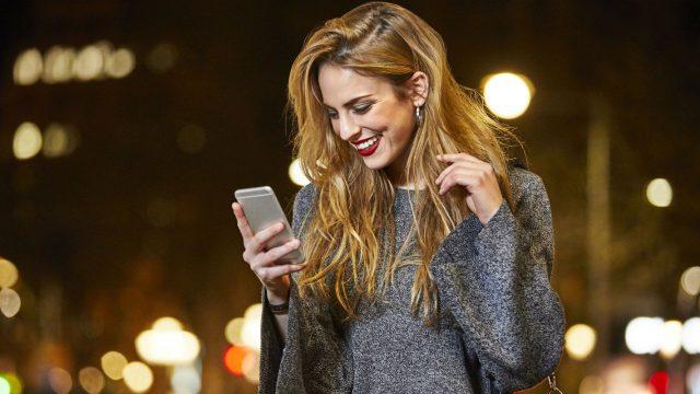 Junge Frau schaut nachts auf ihr Smartphone.