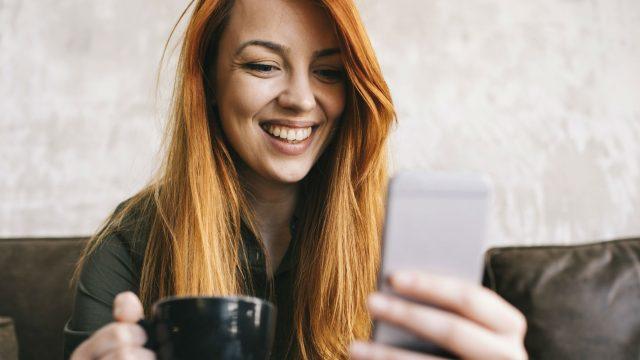Frau mit roten Haaren hält Tasse und Smartphone in der Hand.