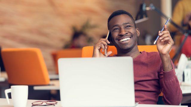 Junger Mann telefoniert lächelnd mit dem Smartphone.