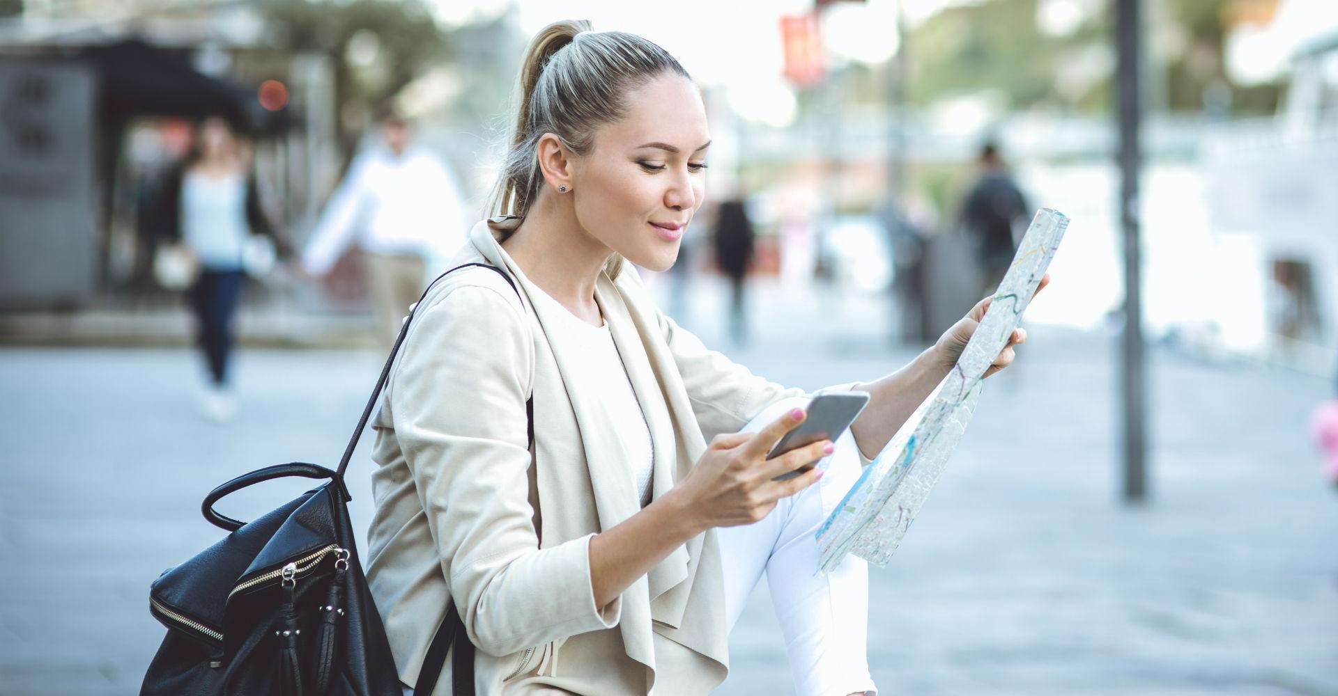 Junge Frau orientiert sich mithilfe von Stadtkarte und Smartphone.