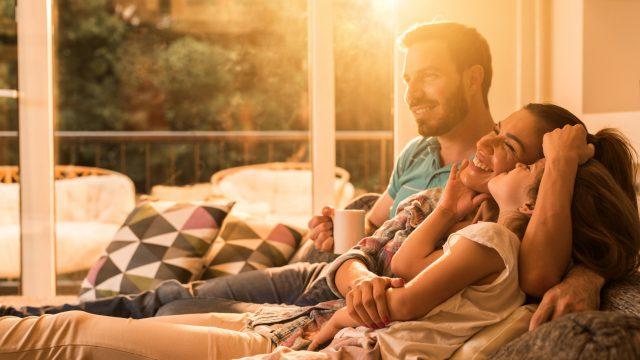Glückliche Familie auf dem Sofa im smarten Zuhause